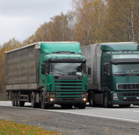 Transportation logistics, European green semi trucks with awning trailers move left to right on asphalt country road on autumn day, front side wide view
