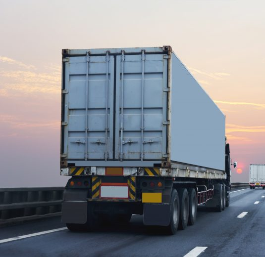 Truck on highway road with container, transportation concept.,import,export logistic industrial Transporting Land transport on the asphalt expressway with sunrise sk